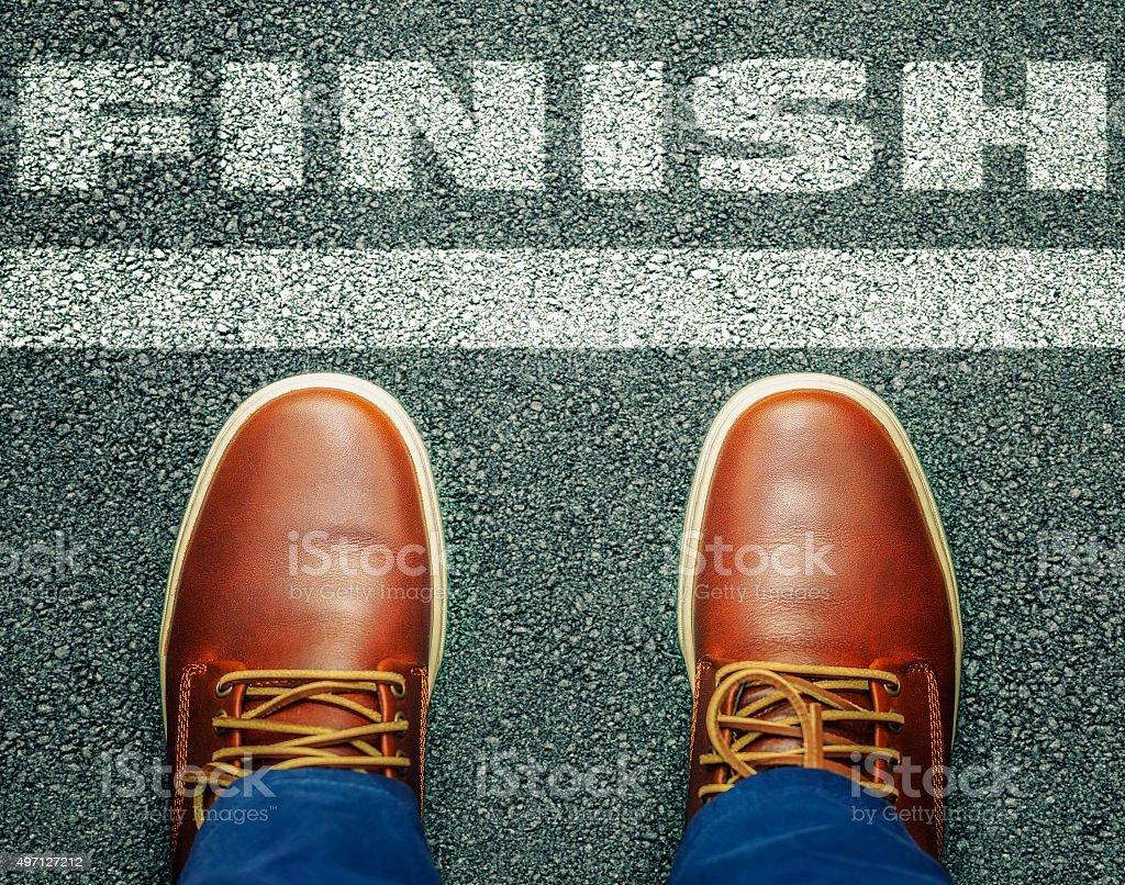 Man before inscription Finish on asphalt stock photo