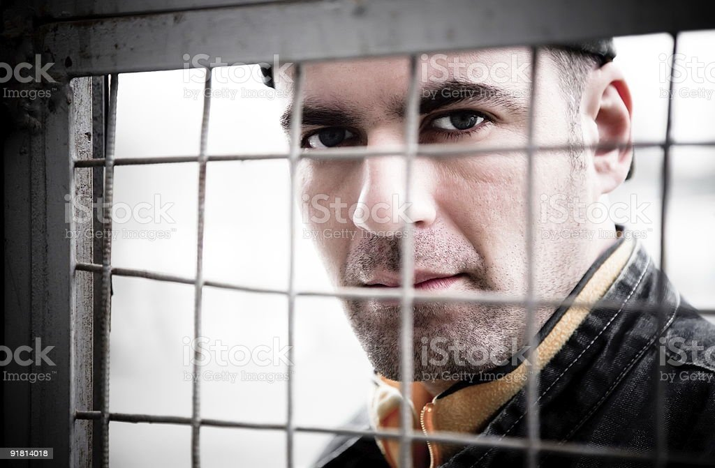 Man Behind An Iron Lattice royalty-free stock photo