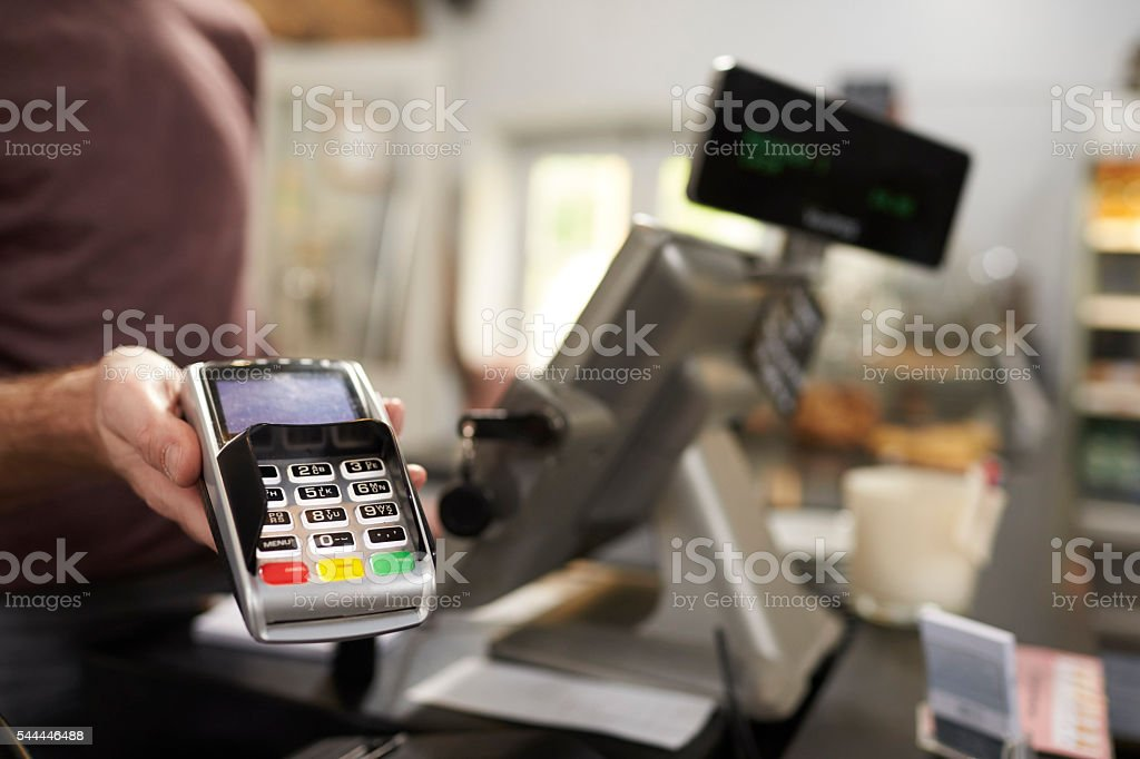 Man behind counter at a cafe offering credit card terminal stock photo