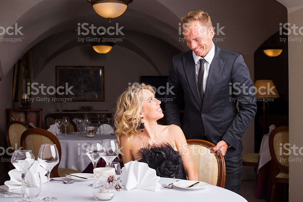 Man being a gentleman and helping woman with her chair stock photo