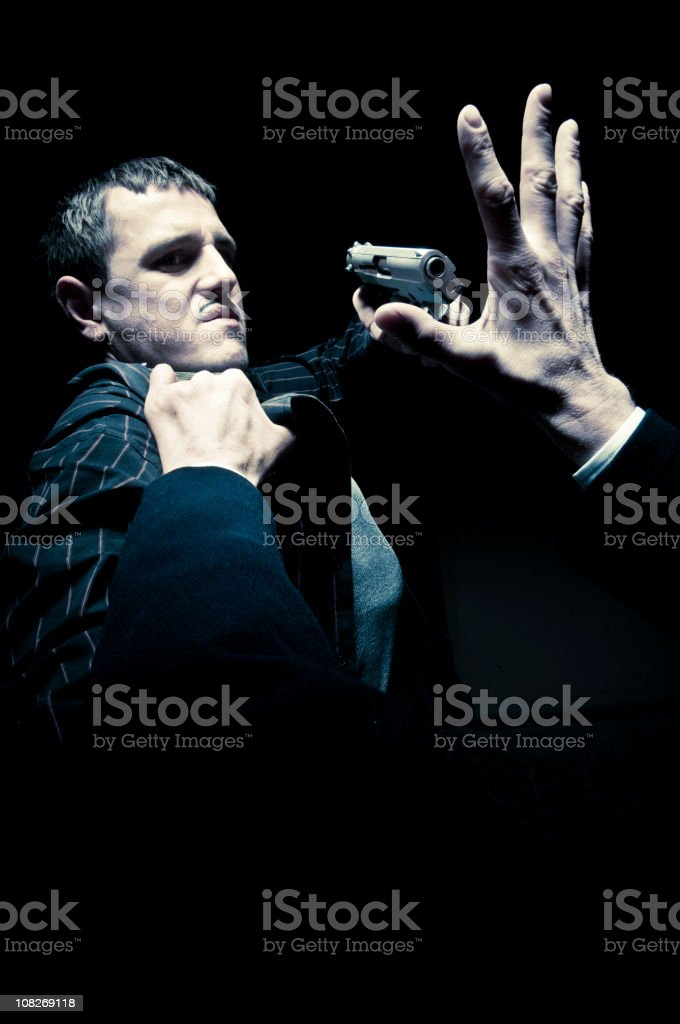 Man Being Grabbed and Holding Gun Up stock photo