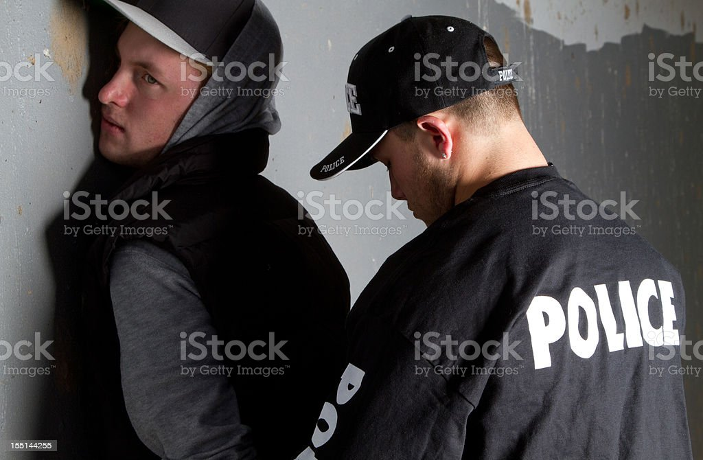 Man being handcuffed by a policeman against a gray wall stock photo