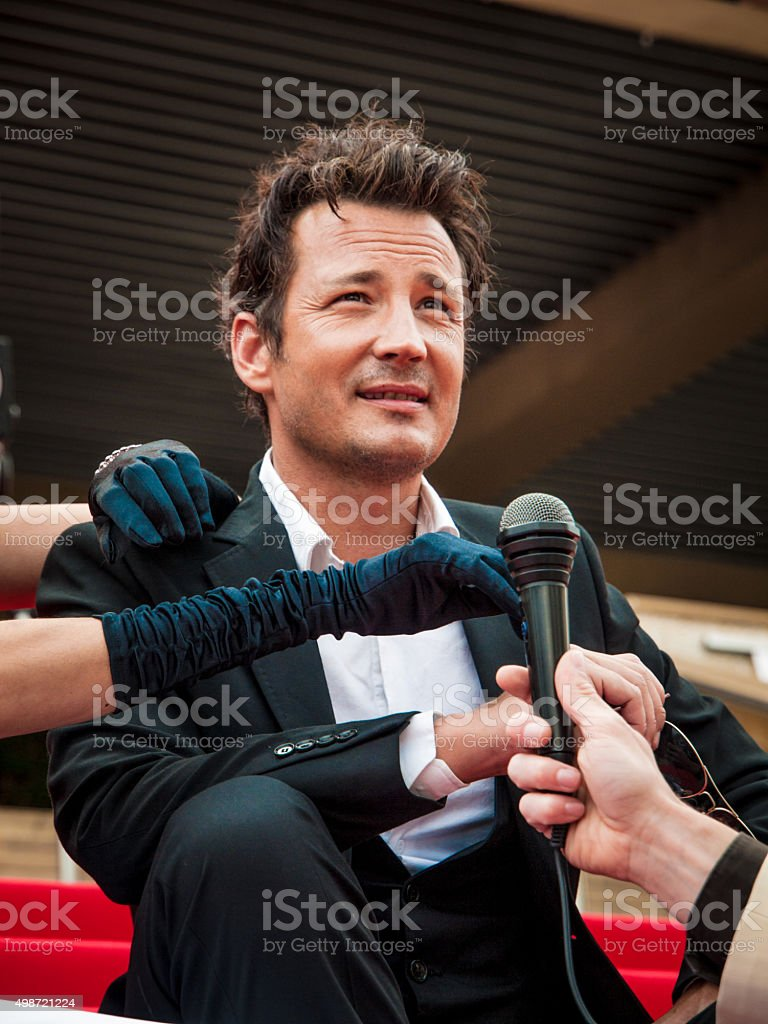 Man being interviewed while sitting on the red carpet stock photo