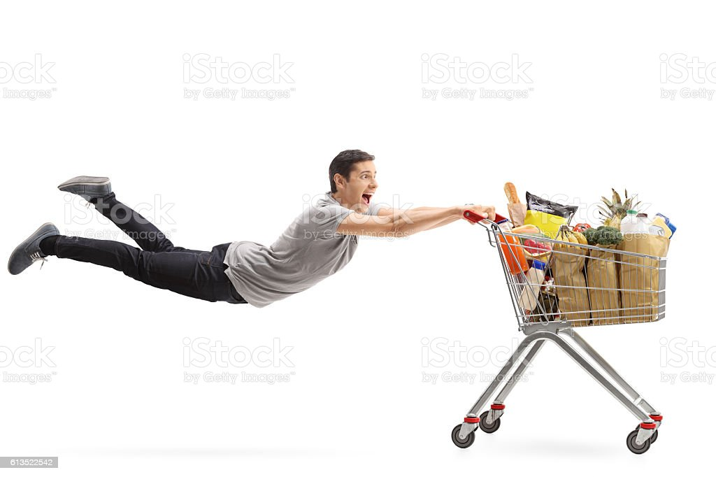 Man being pulled by a shopping cart full of groceries stock photo