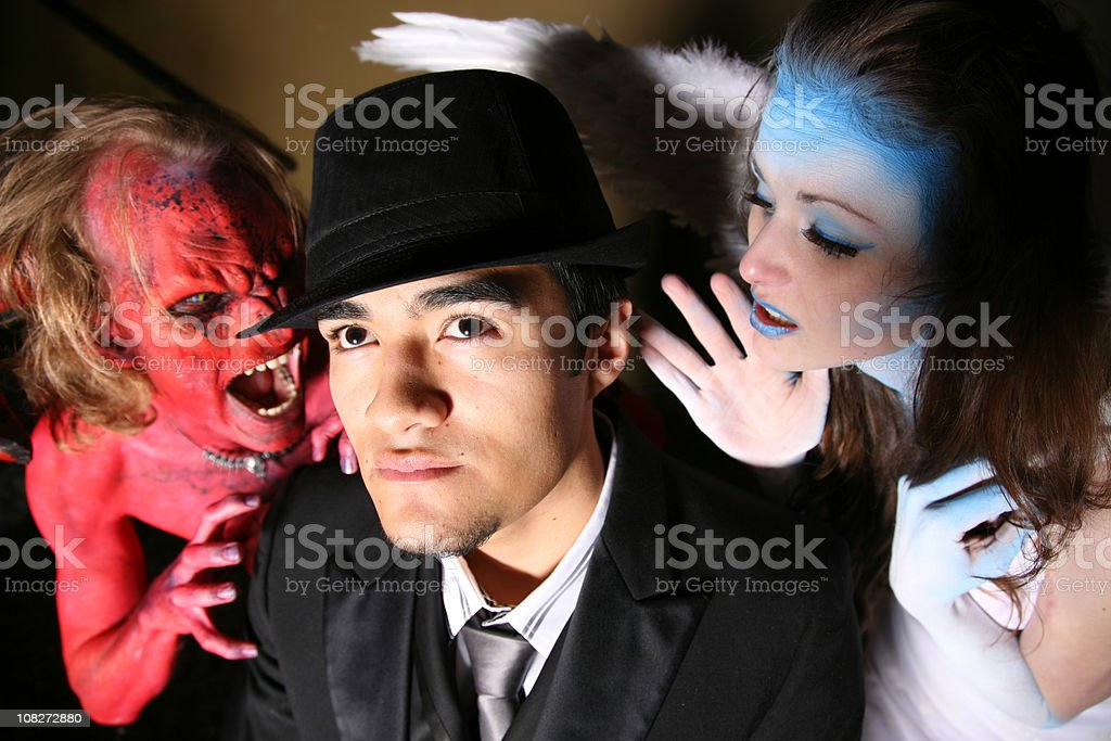 Man being tempted by a devil and an angel royalty-free stock photo