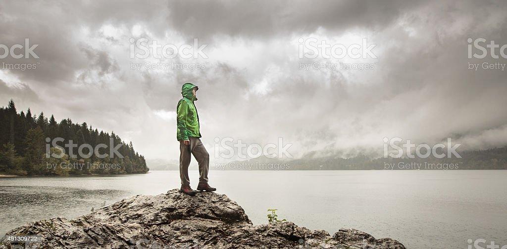 Man beside a mountain lake in rain stock photo