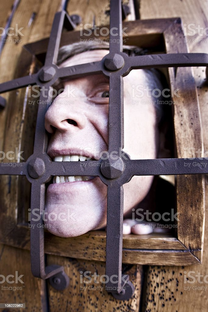 Man Biting Bars of Jail royalty-free stock photo