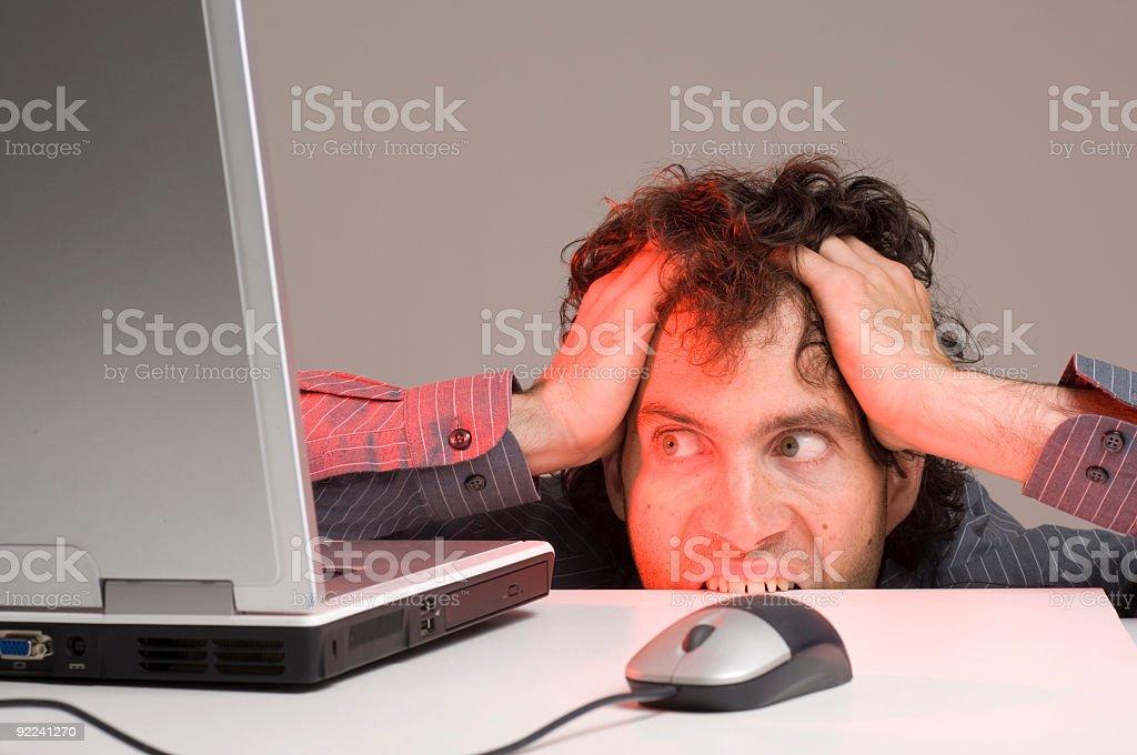 Man biting computer desk royalty-free stock photo