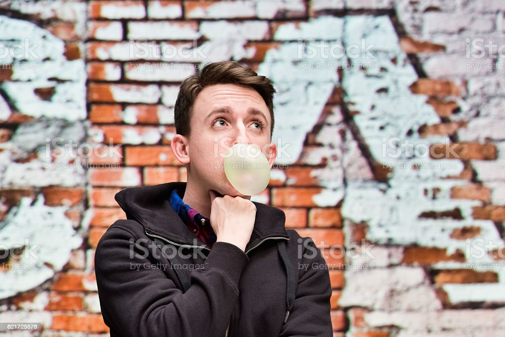 Man blowing bubble gum outdoors stock photo