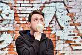 Man blowing bubble gum outdoors