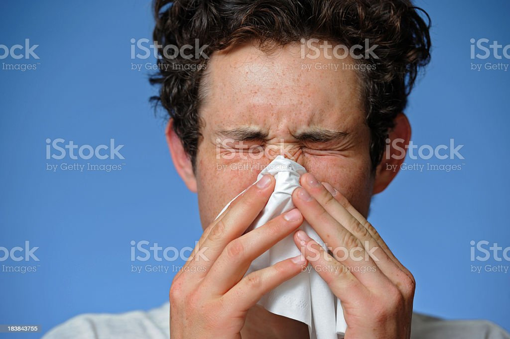 A man blowing his nose into a tissue stock photo