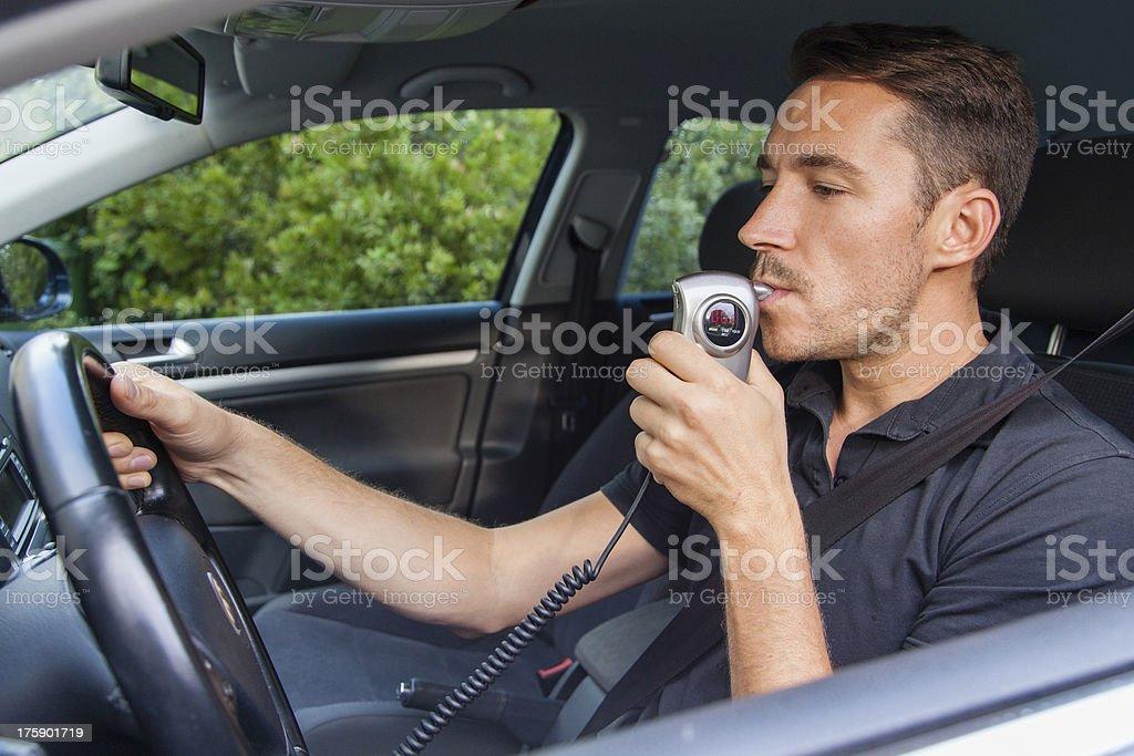 Man blowing into breathalyzer stock photo