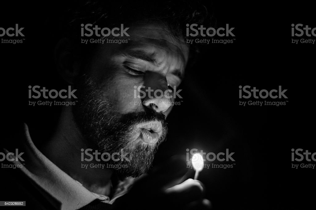 Man blowing matchstick on fire royalty-free stock photo