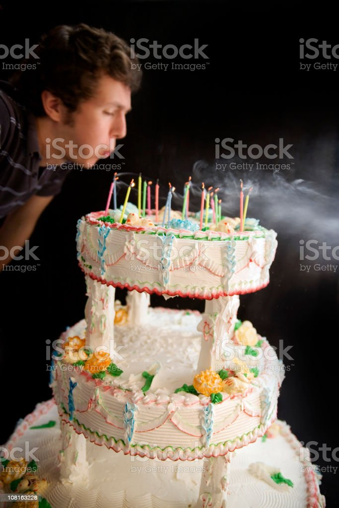 Man Blowing Out Candles on Tiered Cake stock photo