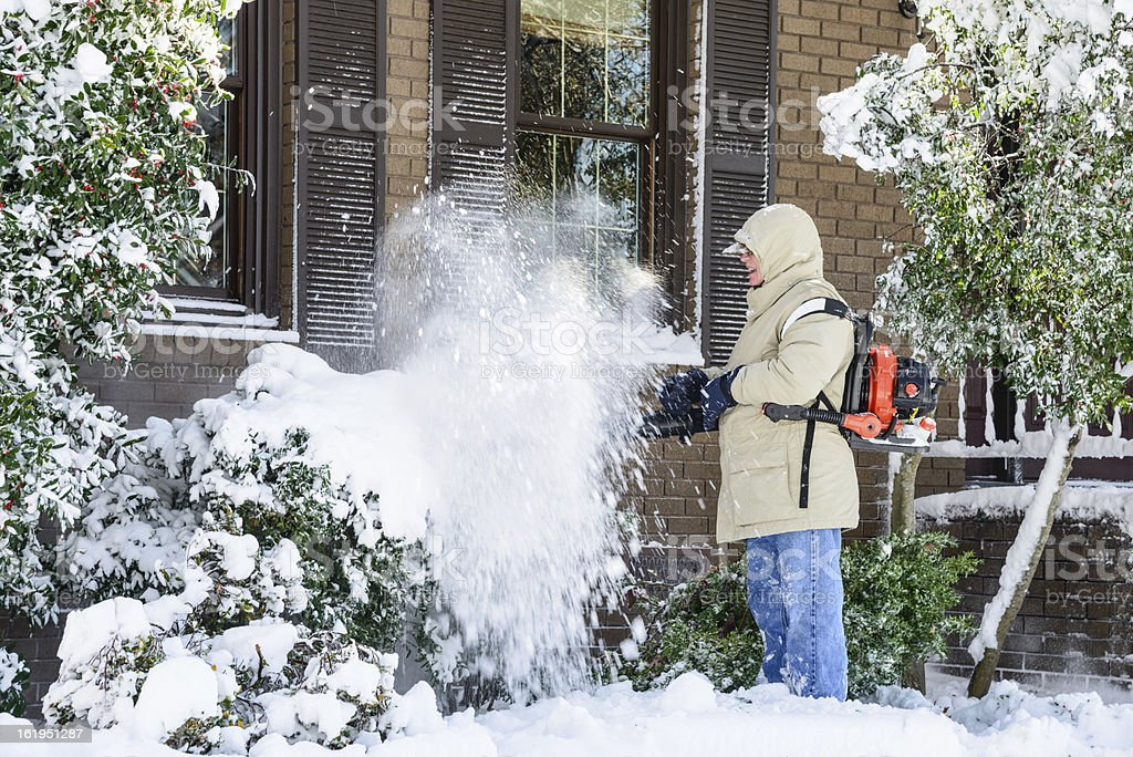 Man blowing snow off bushes stock photo