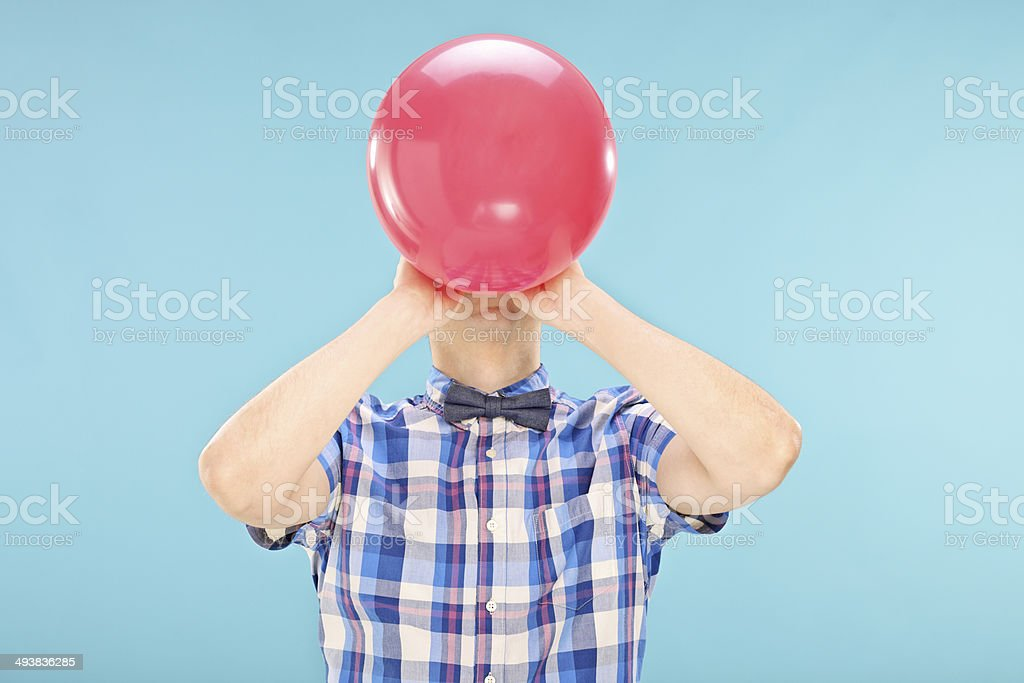 Man blowing up a balloon stock photo