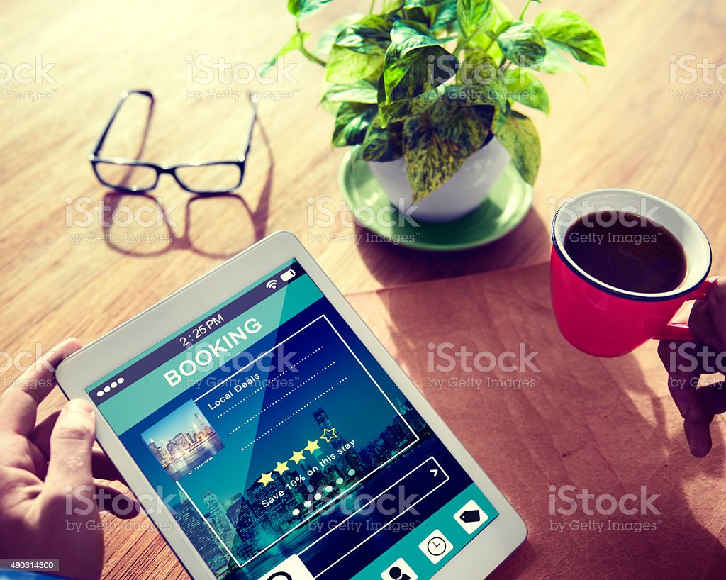 Man Booking Hotel Reservation on Digital Tablet stock photo