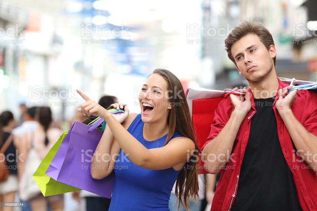 Man bored shopping with his girlfriend stock photo