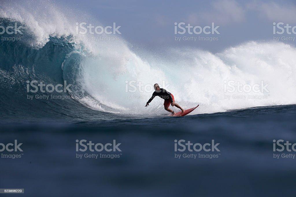 Man bottom turns on a big barreling wave stock photo