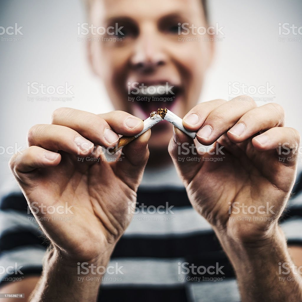 Man breaking a cigarette royalty-free stock photo