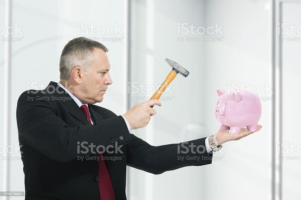 Man breaking a piggy bank royalty-free stock photo