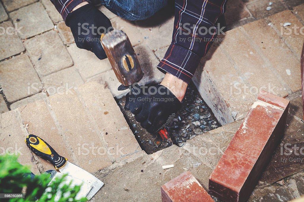 Man breaks masonry hammer and chisel stock photo