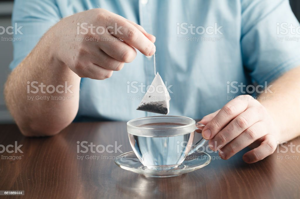 man brewing tea bag with glass of tea on table stock photo