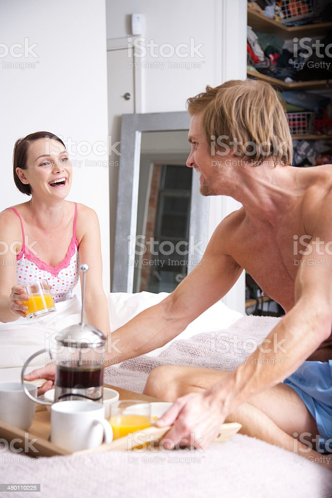 Man bringing a woman breakfast in bed royalty-free stock photo