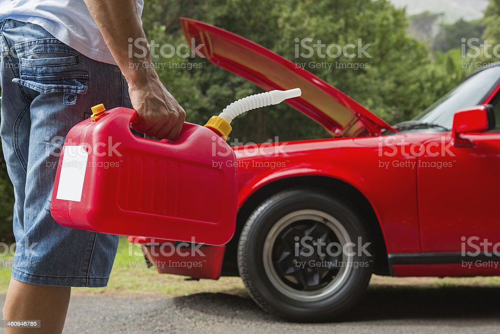 Man bringing petrol refill to a red car stock photo