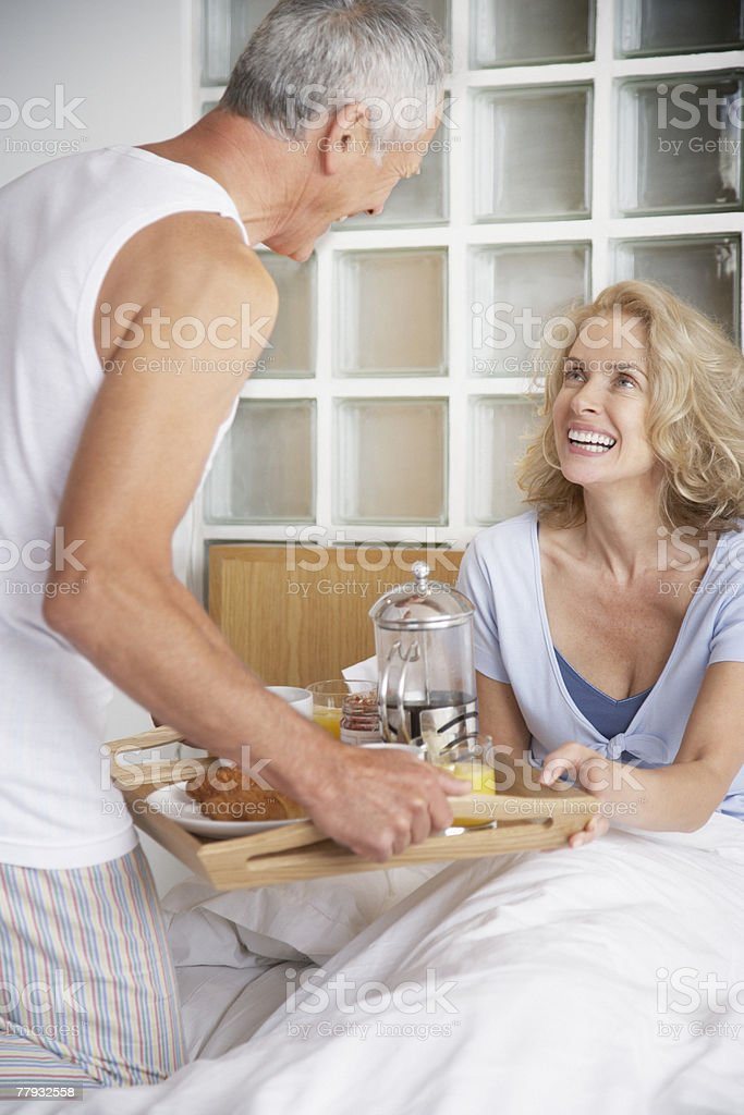 Man bringing woman breakfast in bed royalty-free stock photo