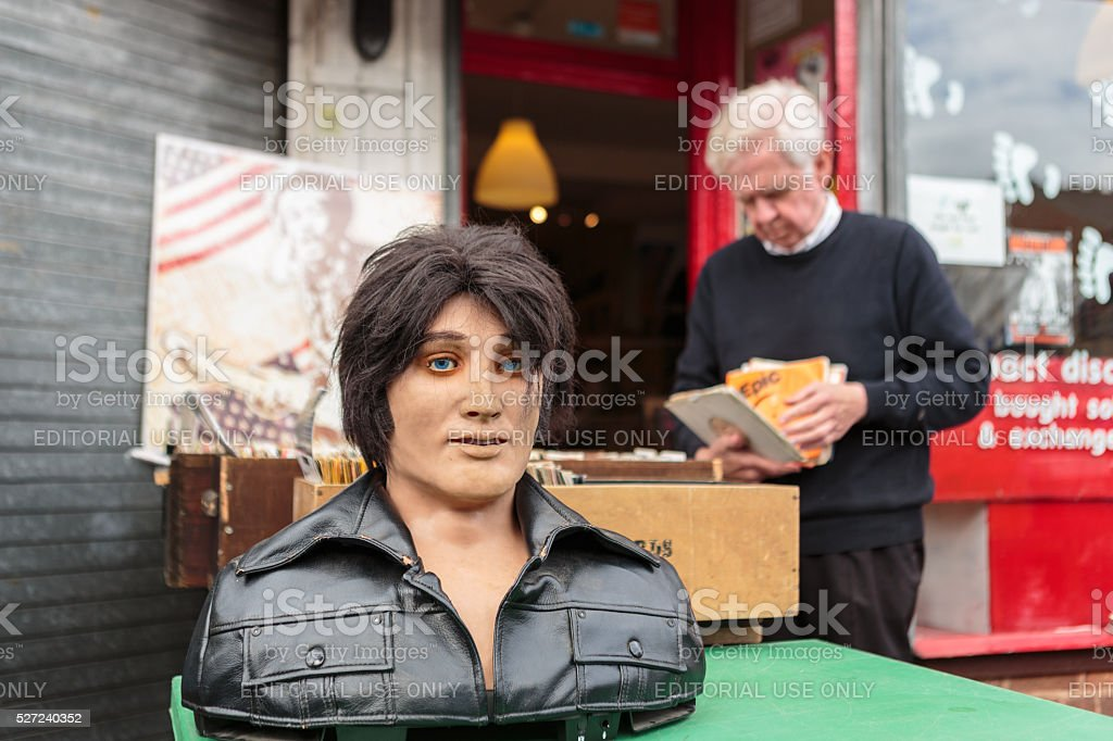 Man browsing records with Elvis bust in foreground stock photo