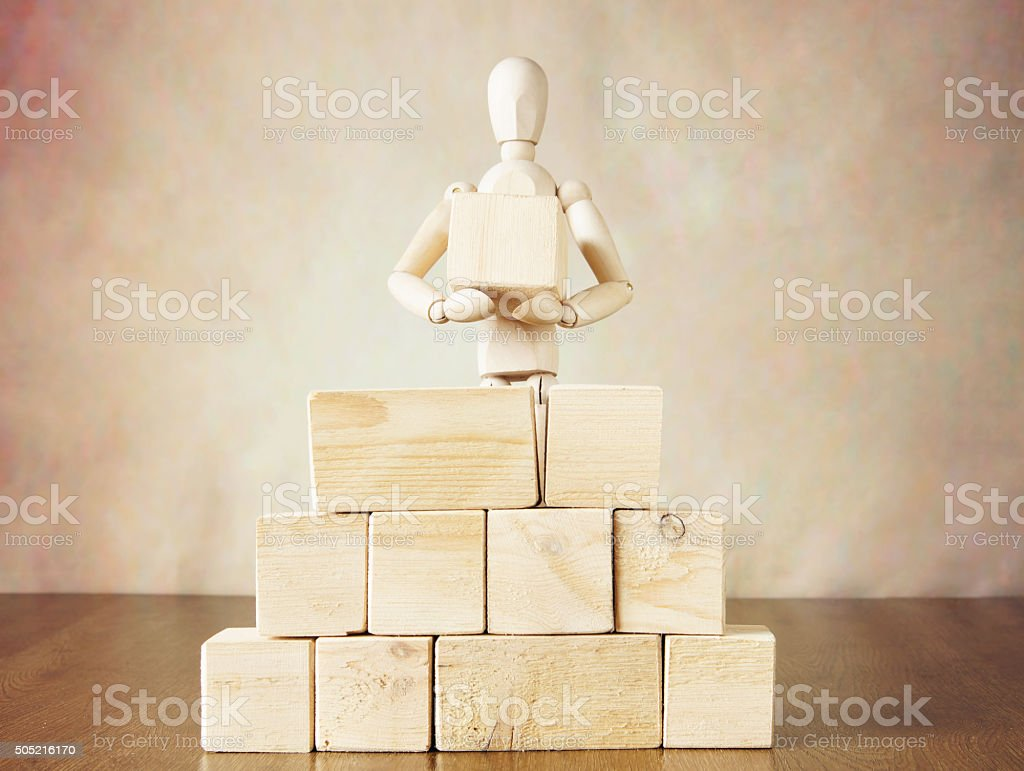 Man building a wall of big blocks. Conceptual image stock photo