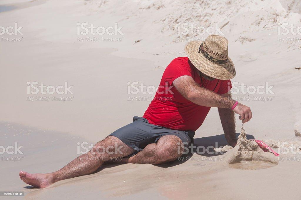 Man Builds a Sandcastle stock photo