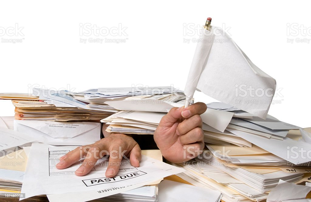 Man Buried in Paperwork with Hands Holding Surrender Flag stock photo