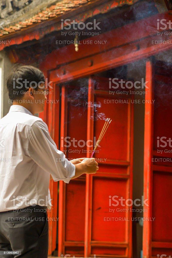 Man Burning Incense at Temple of Jade Mountain, Hanoi, Vietnam. stock photo
