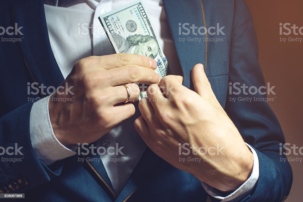 man businessman taking notes in pocket as a bribe stock photo