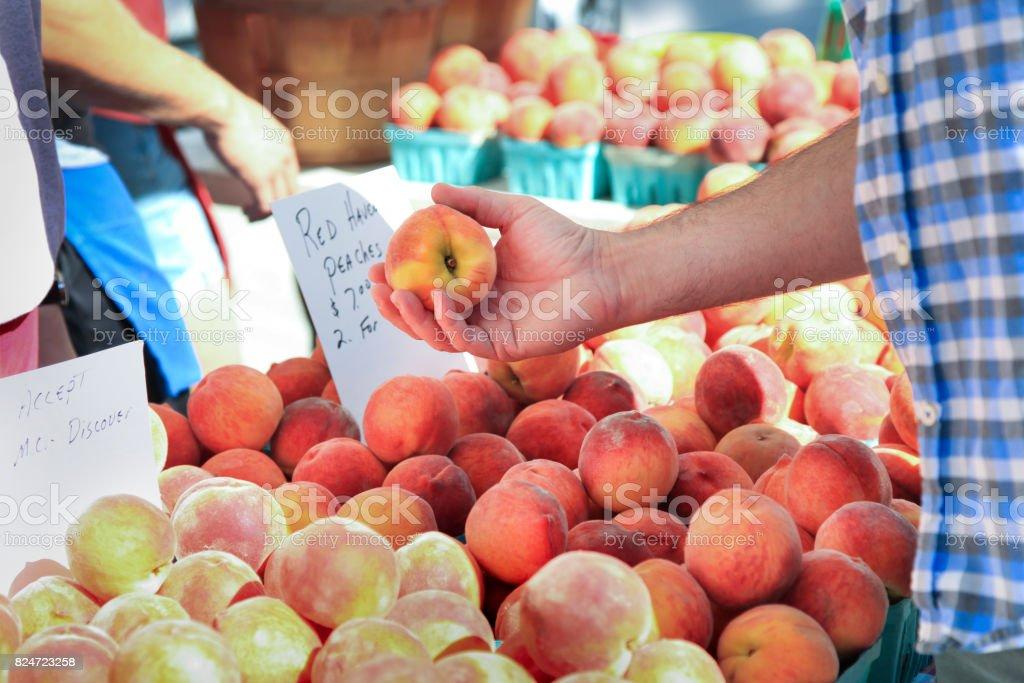 Man Buying Fresh Peaches stock photo