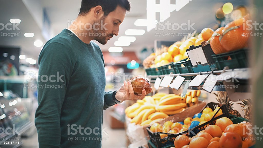 Man buying fruit in supermarket. stock photo