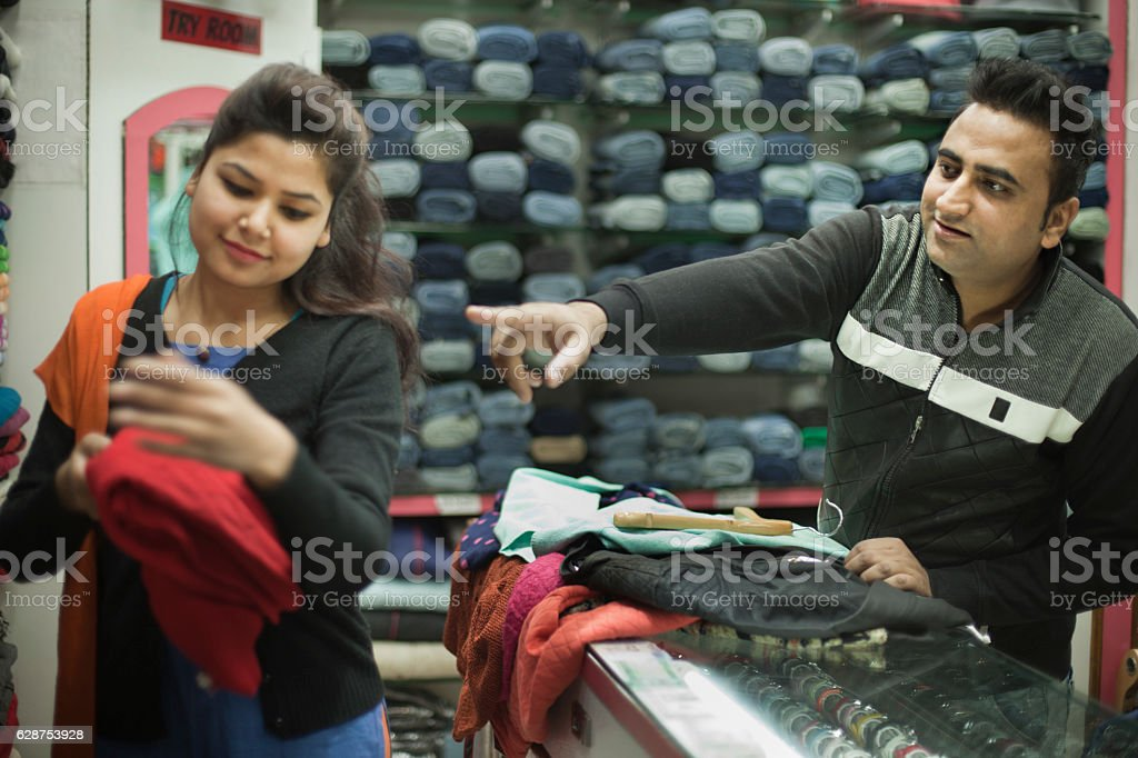 Man buying garments for family and confident saleswoman helping him. stock photo