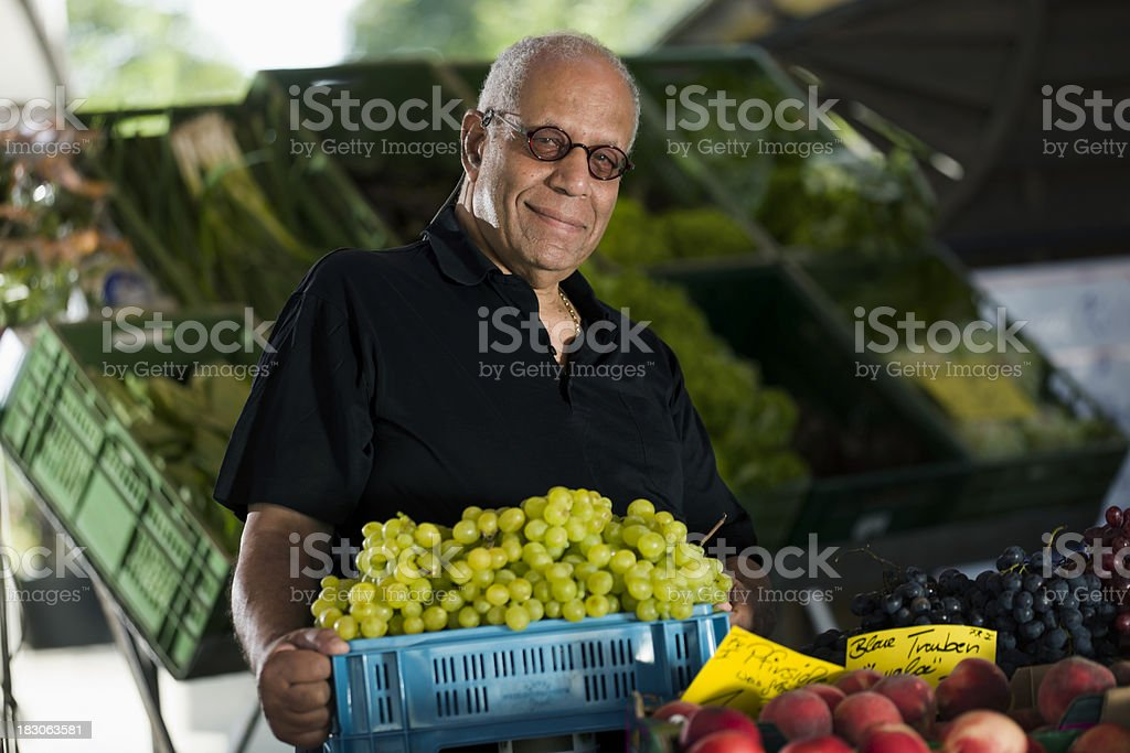 Man Buying Grapes at an Outdoor Market royalty-free stock photo