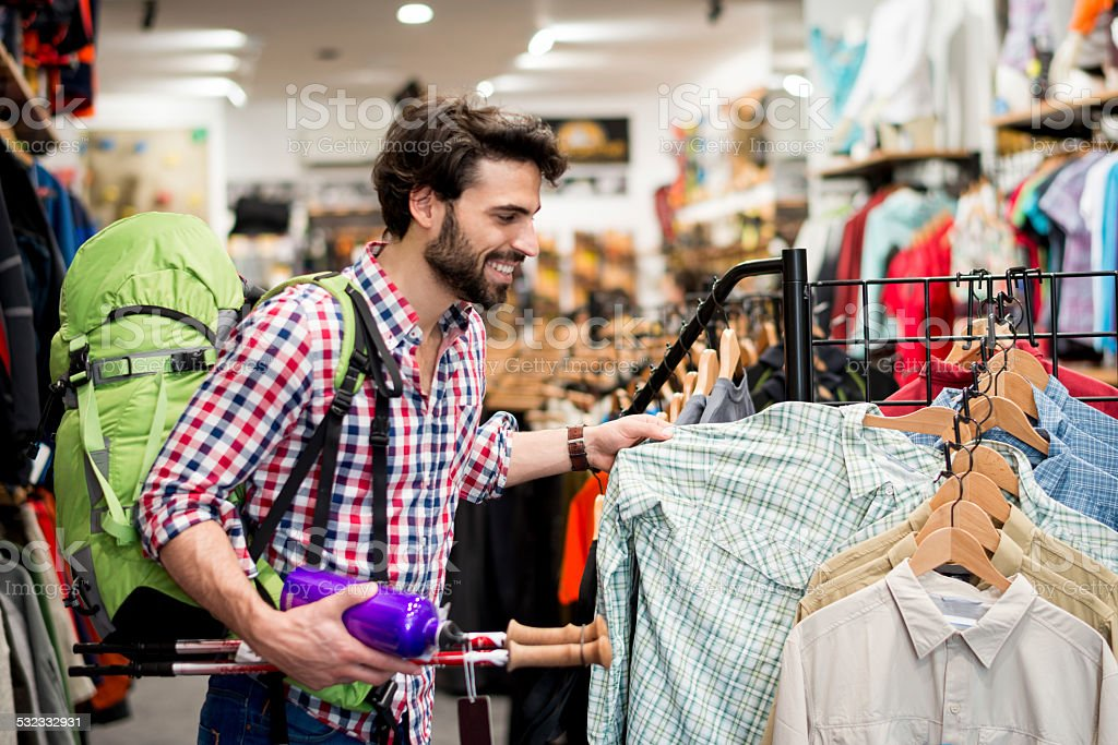 Man buying items in sports and outdoor store stock photo