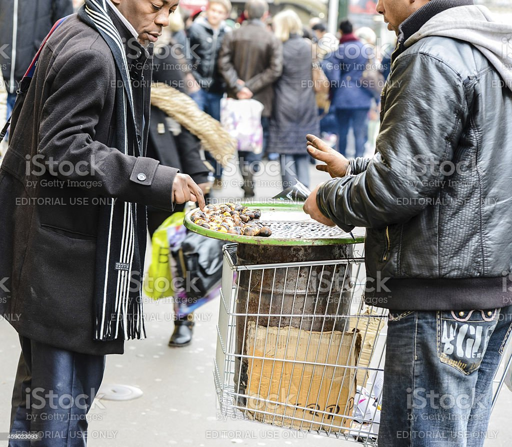 Man buying roasted chestnuts on Paris street royalty-free stock photo