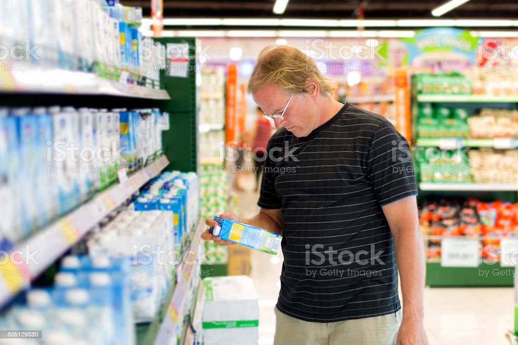 man buys milk stock photo