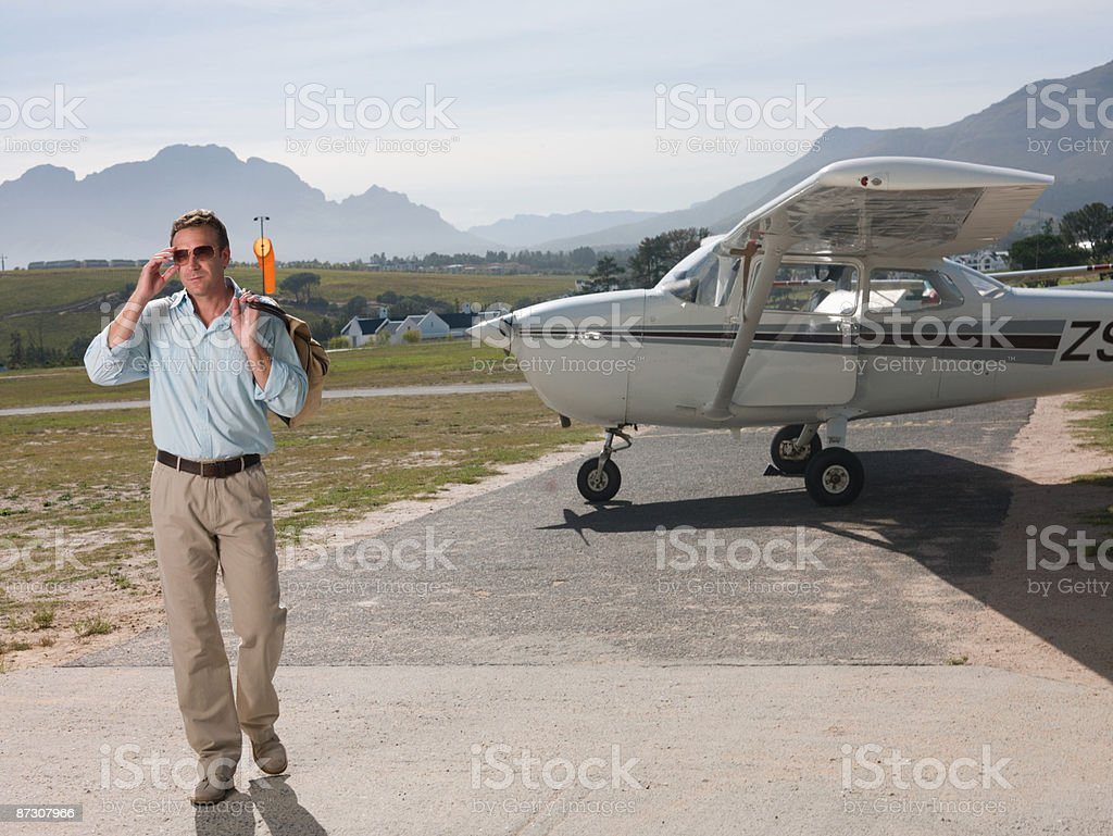 Man by private aeroplane stock photo