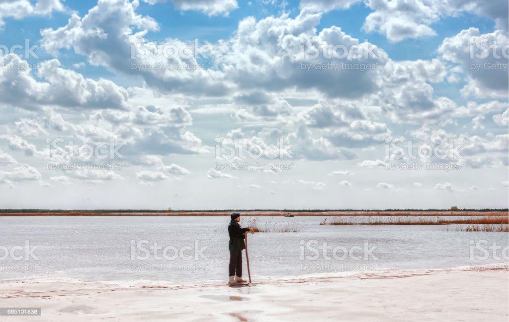 Man By The Lake Among Quartz Sand Under Beautiful Sky stock photo