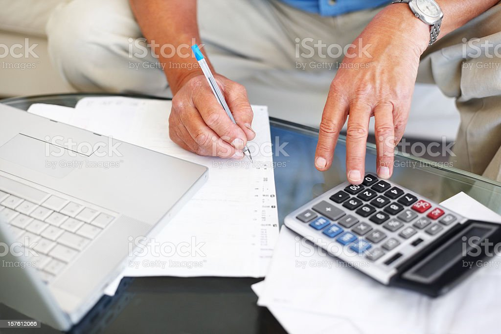 Man calculating budget with laptop and calculator royalty-free stock photo