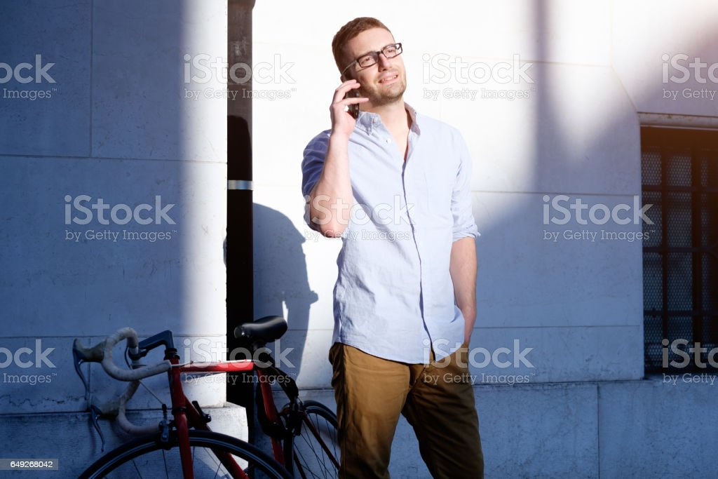 Man calling on his smartphone and walking in the city streets stock photo