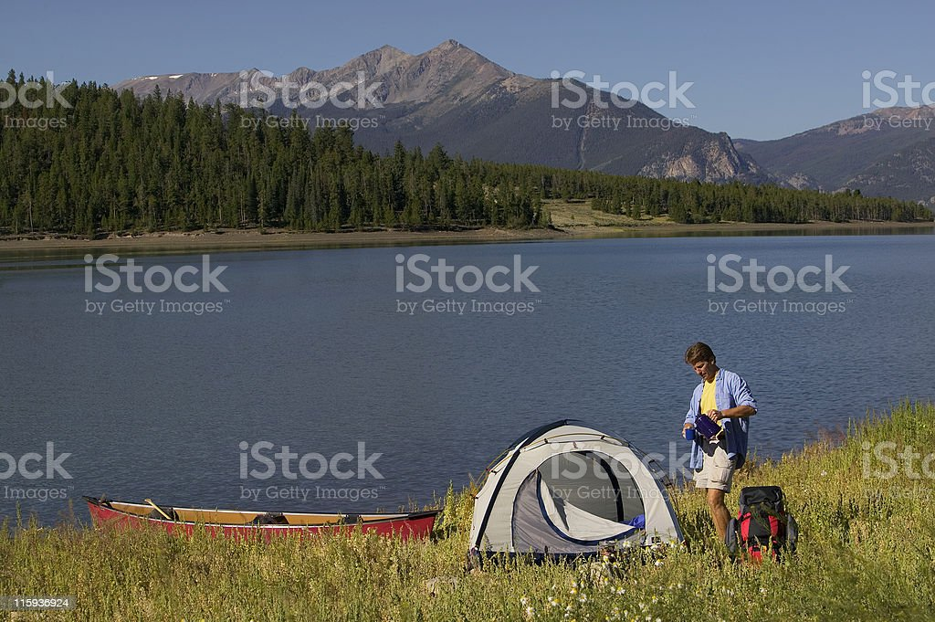 Man Camping by Mountain Lake with Canoe and Tent royalty-free stock photo