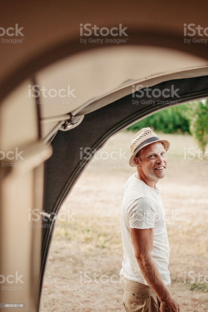 Man camping in his caravan and turning on grill stock photo