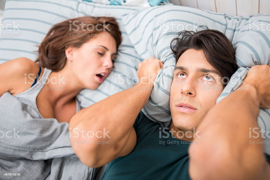 Man cannot sleep because his wife snores stock photo